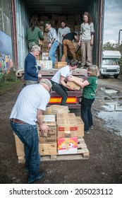 EXETER, UK - MARCH 27: Bookcycle volunteers place boxes onto the back of the container during the loading for books bound for Ghana at the BookCycle warehouse on March 27, 2014 in Exeter, Devon, UK