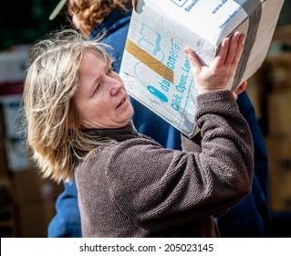 EXETER, UK - MARCH 27: Bookcycle volunteer places boxes onto the back of the container during the loading for books bound for Ghana at the BookCycle warehouse on March 27, 2014 in Exeter, Devon, UK