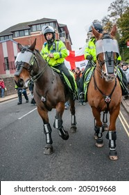 EXETER, UK - NOVEMBER 16: Police horses lead English Defence League march along New North Street during the English Defence League march and rally November 16, 2013 in Exeter, Devon, UK