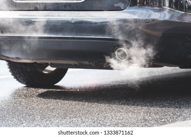 exhaust gas coming out of an exhaust pipe of a car on a street