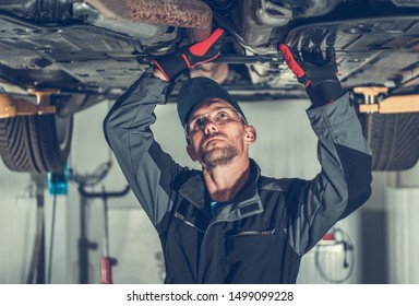 Exhaust Lambda Probe Check. Professional Auto Service Mechanic Looking For Issues with Modern Vehicle While Checking Car Under Carriage.