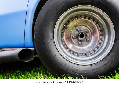 The exhaust and tire of an American made sixties sports car.