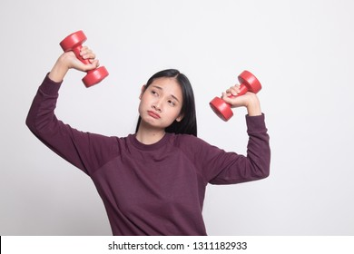 Exhausted Asian woman with dumbbells on white background