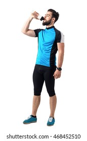 Exhausted athlete in bicycling sportswear drinking water from plastic bottle.  Full body length portrait isolated over white studio background.