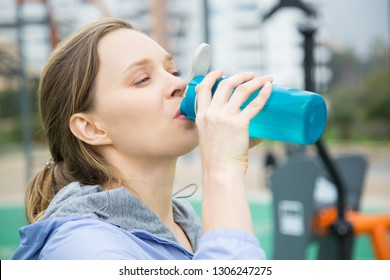 Exhausted athlete drinking between exercises. Closeup of young woman in sports hoodie drinking water from blue flask or shaker. Sport and electrolyte balance concept