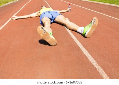 An exhausted athlete on a running track wearing broken green running shoes with big holes in the sole.
