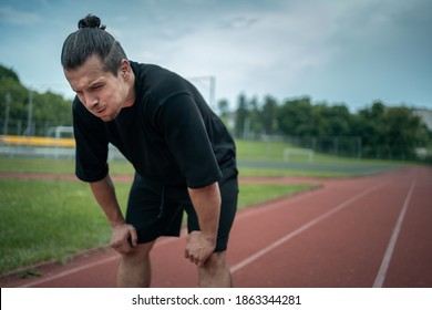 exhausted athlete resting on track after running or workout exercising outdoor