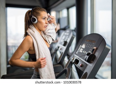 Exhausted beautiful woman on a treadmill at the gym with a towel