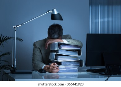 Exhausted businessman leaning head on binders while working late in office