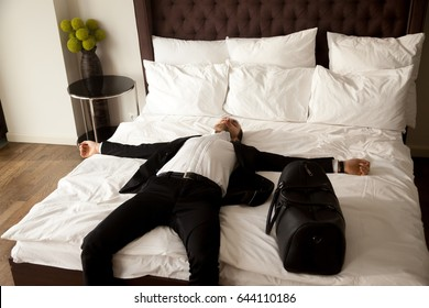 Exhausted businessman resting on bed after long air flight, jet lag. Man in business suit lying with arms outstretched on mattress in hotel room. Happy buyer sleeping in new comfortable house room
