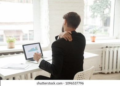 Exhausted businessman stretching at workplace in office, tired after long working hours. Male entrepreneur massaging back suffering from strain, sedentary work and uncomfortable sitting. Back view