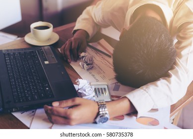 Exhausted businessman surrendering to fatigue working. Stress management makes man tired. Male sleep on desk during job with laptops at coffee shop. Business concept