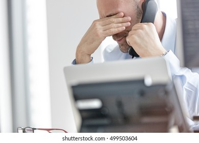 Exhausted businessman using landline phone in office