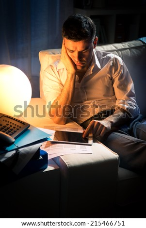 Exhausted businessman working late at night in the living room holding a tablet.