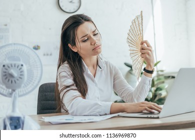exhausted businesswoman using laptop while conditioning air with electric fan and hand fan in office