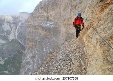 "Exhausted climber along steel cable of via ferrata ""Lipella"", Tofana massif, Dolomite Alps, Italy"
