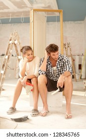 Exhausted couple sitting in bad mood in house under construction.