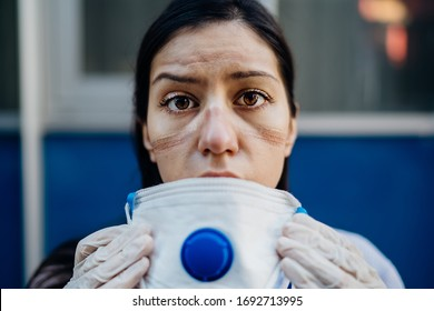 Exhausted doctor / nurse taking of coronavirus protective gear N95 mask uniform.Coronavirus Covid-19 outbrek.Mental state of medical professional.Face scars.Mask shortage.Overworked health workers