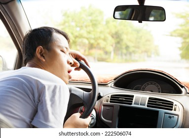 Exhausted driver resting on steering wheel in the car
