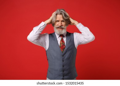 Exhausted elderly gray-haired mustache bearded man in classic shirt vest colorful tie isolated on red background, studio portrait. People lifestyle concept. Mock up copy space. Putting hands on head