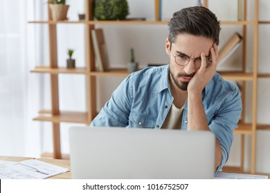 Exhausted embarrassed male reads some information on laptop computer, being tired and overworked after hard work at office all day long, doesn`t understand how make project, being frustrated