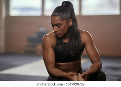 Exhausted ethnic female athlete with rope sitting on haunches and breathing heavily with closed eyes during break in training on blurred background of gym