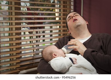 An exhausted father feeds young child in the morning