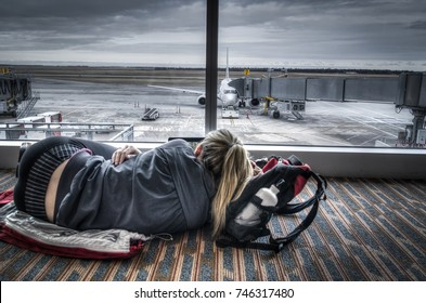Exhausted female traveler lying on the floor in an airport, looking out the window on a overcast dreary day
