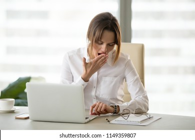 Exhausted female worker yawning looking at watch, waiting for working day to be over