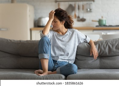 Exhausted frustrated young woman touching forehead, sitting on couch alone, suffering from strong headache or migraine, worried girl thinking about problems, divorce or break up, lost in thoughts
