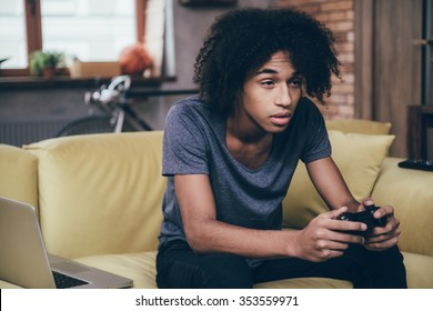 Exhausted gamer. Young African man holding joystick and looking exhausted while sitting on the couch at home