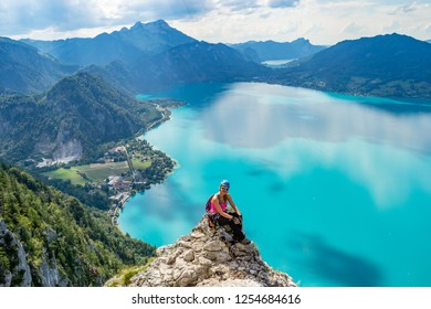 Exhausted but happy girl taking a break on a rock cliff above the turquise waters of Attersee lake, in Upper Austria, during a via ferrata route, on a bright, sunny, summer day.