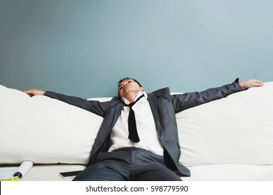 Exhausted, Illness, tired, stressed from overworked concepts. Businessman in grey suit sit on sofa. Senior man sleepy.