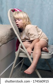 Exhausted little girl just fall asleep straight on the chair