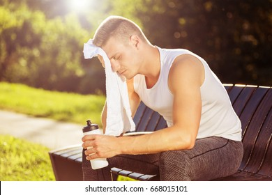 Exhausted male after exercise drinking water and wiping sweat with towel.Tired man resting from sport training Image is intentionally toned.