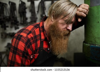 Exhausted male blacksmith with blond hair and long beard leaning on metal tube while standing in workshop and being without strength