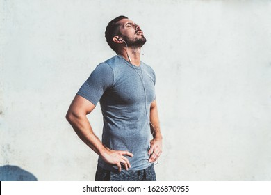 Exhausted male with hands on waist and closed eyes in sportswear with earphones listening to music resting after run in urban street. Copy space area
