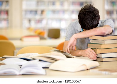 Exhausted male student with a pile of books