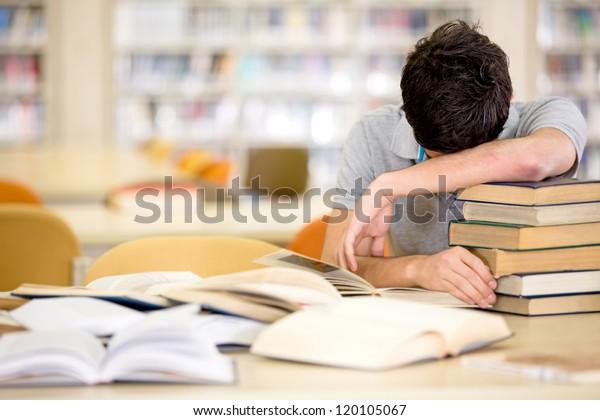 山積みの本を持つ疲れ果てた男の学生
