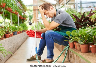 Exhausted man with burnout sitting in a nursery shop