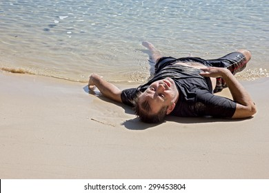 exhausted man crawled out of the sea and lying on the beach