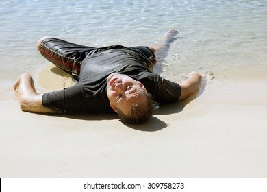 Exhausted man crawled out of the sea and lying on the beach. Almost drowned person at the seashore. Survive the shipwreck in the ocean.
