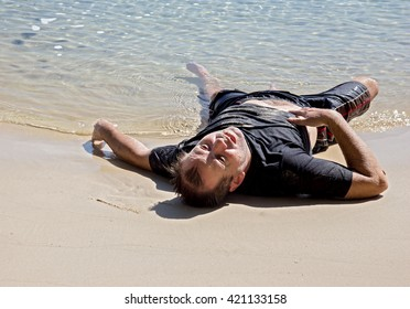 Exhausted man crawled out of the sea and lying on the beach. Castaway lying on the coast.