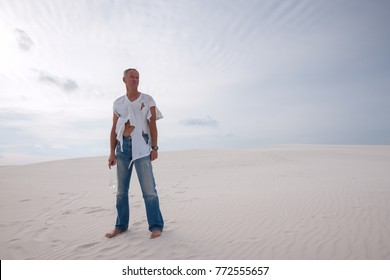 Exhausted man, lost in the desert, is standing on a sand dune, in worn out clothes, and looking hopefully into the distance. Desert before a storm. Wide angle.