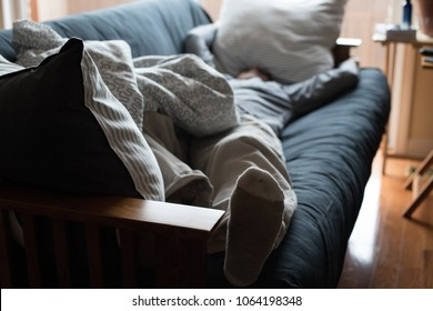 Exhausted man napping on a couch with his head under a pillow.