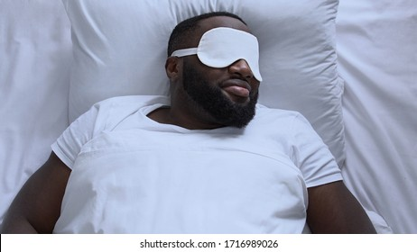 Exhausted man in sleep mask trying to fall asleep after long flight, jet lag