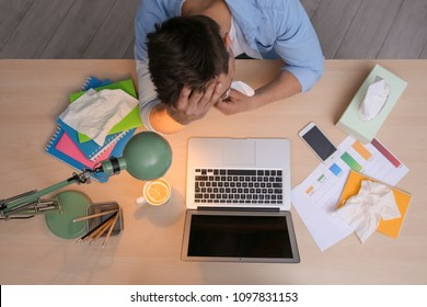Exhausted man with tissue suffering from cold while working with laptop at table, top view