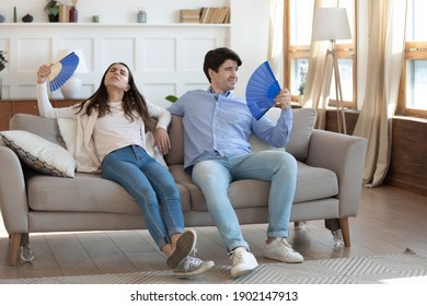 Exhausted man and woman waving blue paper fans, breathing, resting sitting on couch in living room, overheated tired couple suffering from hot summer weather, heating at home, feeling discomfort