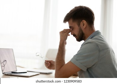 Exhausted man worker massage nose bridge suffer from dizziness or blurry vision, tired male take off glasses sit with eyes closed having headache or eye tension, guy take break from work feel unwell