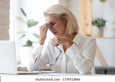 Exhausted mature female employee sit at desk take off glasses massage eyes suffer from headache migraine, tired middle-aged businesswoman have dizziness or blurry vision, health problem concept